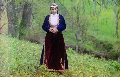 Armenian woman in national costume poses of Prokudin-Gorskii on a hillside near Artvin, circa 1910.
